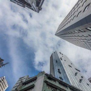 Immobilien Portfolio Optimierung buchen- BIld von unten an hohen Häusern hinauf